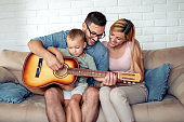 Cheerful parents are playing with son at home