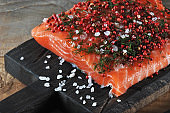 A piece of fresh salmon on a wooden board in the process of pickling. The surface of the fish is abundantly sprinkled with large sea salt, pink pepper and dill.