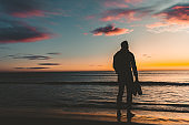 Young man walking down the beach at sunrise.