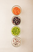 Collection set of various dried legumes in glass glasses arranged vertically green peas, red lentils, red beans, white beans close-up on a white background