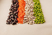 Collection set of various dried legumes laid out in a horizontal line: red lentils,green peas, red beans, white beans close-up on a white background. Selective focus