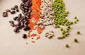 Collection set of various dried legumes laid out in a horizontal line, chaotic order: red lentils,green peas, red beans, white beans close-up on a white background. Selective focus