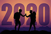 People giving high five silhouette with big new year 2020 and sunset