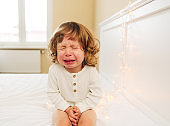 Tearful little girl.Small cute girl is crying on the bed at home.indoor.baby with tears.curly hair and blue eyes.
