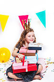 Happy little pretty girl sitting with presents at birthday party