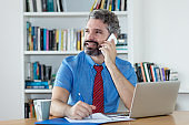 Mature financial advisor with beard talking with client