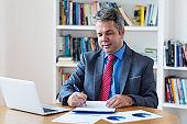 Mature german businessman working at desk
