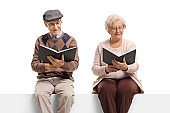 Elderly man and woman seated on a panel reading books