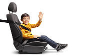 Little boy in a car seat with a fastened seatbelt looking at the camera and waving