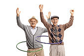 Two cheerful senior men spininng hula hoops