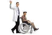 Young male doctor waving and pushing an elderly male patient in a wheelchair