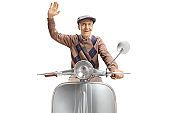 Cheerful elderly man riding a vintage scooter and waving