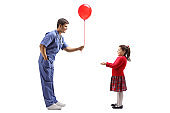 Male doctor giving a red balloon to a little girl