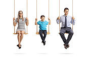 Happy family of a mother, father and son sitting on swings and looking at the camera