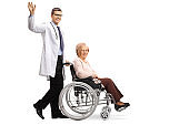 Young smiling positive male doctor waving and pushing a disabled senior woman in a wheelchair