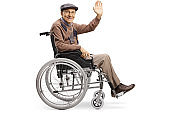 Senior disabled man waving from a wheelchair
