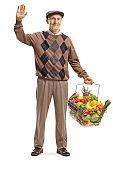 Senior man carrying a full shopping basket and waving at the camera