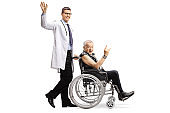Male doctor waving and pushing a mature male patient making a rock and roll hand sign in a wheelchair