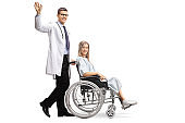 Young male doctor waving and pushing a female patient in a wheelchair