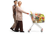 Elderly couple walking and pushing a shopping cart with food products