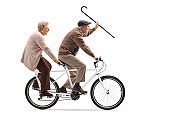 Senior man and woman riding a tandem bicycle and waving with a walking cane