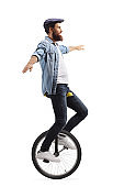 Young man on a unicycle balancing with hands