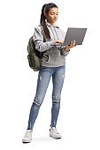 Female student standing and typing on a laptop