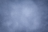 Background of light blue suede fabric closeup. Velvet matt texture of steel nubuck textile