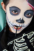Little girl in halloween zombie makeup costume at home