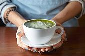 Woman holding Matcha green tea latte on wooden table