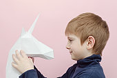 White paper unicorn and little boy.  Pink background.