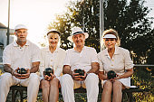 Senior people sitting together on a bench in a park holding boules