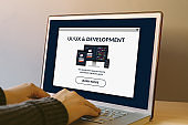 UI/UX design and development concept on laptop screen on wooden table