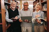 Cheerful senior colleagues standing in a library