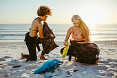 Girls picking up trash from the beach