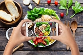 Hand hold smartphone woman takes photo healthy food for blog,photographer food