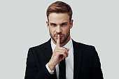 Handsome young man in formalwear looking at camera and keeping finger on lips while standing against grey background