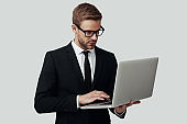 Handsome young man in formalwear working using laptop while standing against grey background