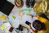 Vacation travel planning concept with map. Overhead view of equipment for travelers. Travel concept background, Young woman pointing to the map India.