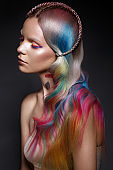 Beautiful girl with multi-colored hair and creative make-up and hairstyle. Beauty face.
