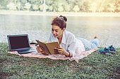 Women sitting a relax working with a notebook and lying reading a book during a relax in the park. in the holiday. summer