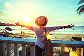 Asian woman travel nature. Travel relax. Happy with the stand and extend the arms see the sunset on the beach. In the summer