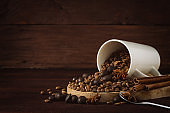 Coffee Grain is poured from the White Cup, Cinnamon, Chocolate Balls on a dark wooden background. Copy space