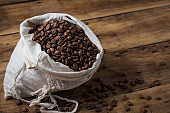 Bag of coffee beans on a wooden background