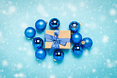 Gift box with blue ribbon, blue Christmas tree toys, balls on a blue background with falling snow. Concept of Merry Christmas and Happy New Year. Flat lay, top view