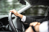 Cropped hands of man driving car