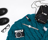 Flat lay top view female casual style look with warm turquoise sweater, jeans, boots, watch, glasses and purse.