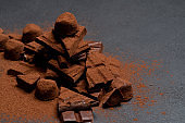 Dark or milk organic chocolate pieces, cocoa powder and truffle candies on dark concrete backgound
