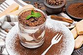 Classic tiramisu dessert in a glass on wooden background