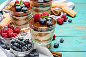 Classic tiramisu dessert with blueberries and strawberries in a glass cup and savoiardi cookies on wooden background